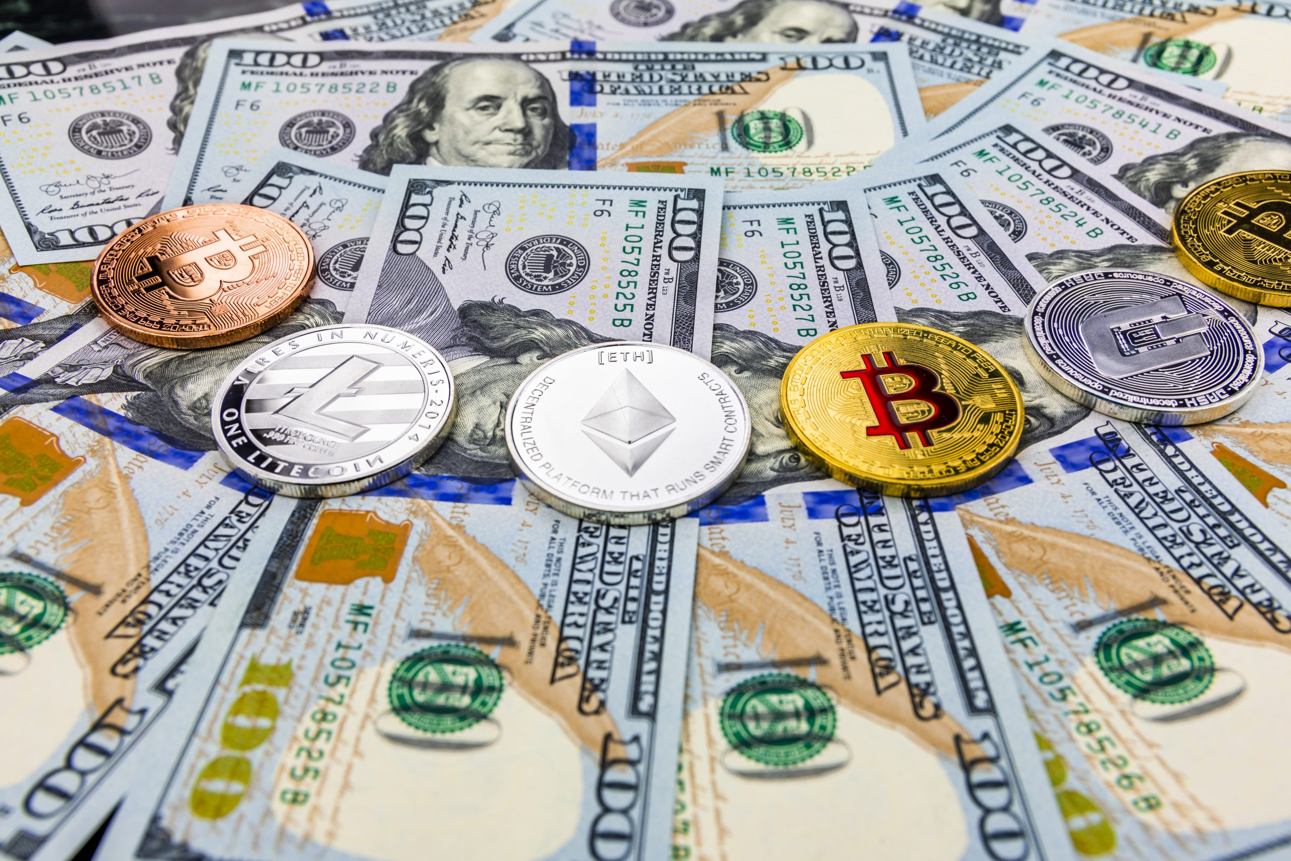 Bitcoin and cryptocurrency on banknotes of one hundred dollars.